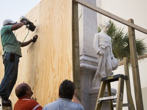 Workers place boards around a Confederate monument on Hillsborough County property in Tampa, Fla., Thursday, Aug. 17, 2017. In a divisive 4-2 vote Wednesday, Hillsborough County commissioners gave fundraisers 30 days to collect $140,000, about half of what's needed to relocate the monument from its spot in front of a courthouse annex in downtown Tampa.