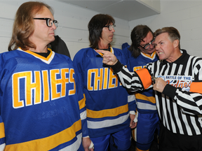 """In this Sept. 26, 2011 file photo, the """"Hanson Brothers"""" — from left, Dave Hanson, Steve Carlson and Geoff Carlson — are shown with former NHL referee Kerry Fraser."""