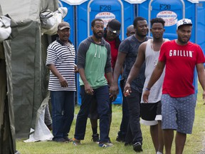 Asylum seekers step out of a tent to receive lunch at the Canada-United States border in Lacolle, Que. Thursday, August 10, 2017. THE CANADIAN PRESS/Graham Hughes
