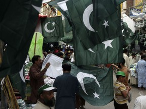 People buy flags to celebrate Pakistan's independence day, in Lahore, Pakistan, Sunday, Aug. 13, 2017. The nation will celebrate their 70th Independence Day on Monday, having gained its independence from British colonial rule in 1947. (AP Photo/K.M. Chaudary)