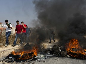 Palestinian protesters burn tires and clash with Israeli army soldiers after troops searched and measured the family house of Omar al-Abed, 20, identified by the Israeli army as the assailant of yesterday's attack at the Israeli settlement of Halamish, in preparation for demolition, in the West Bank village of Kobar, near Ramallah, Saturday, July 22, 2017.