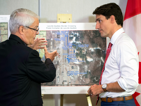 Prime Minister Justin Trudeau is briefed on the refugee installations at the Lacolle border crossing, Aug. 23, 2017 in Montreal.
