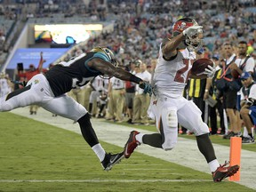 Tampa Bay Buccaneers running back Doug Martin (22) runs for a 2-yard touchdown past Jacksonville Jaguars linebacker Telvin Smith (50) during the first half of an NFL preseason football game, Thursday, Aug. 17, 2017, in Jacksonville, Fla. (AP Photo/Phelan M. Ebenhack)