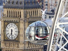 British athlete Mo Farah stands atop of a pod on the London Eye, with Big Ben's clock tower in background, as he bids a final farewell to British track competitive athletics after winning gold in the 10,000m and silver in the 5,000m at the IAAF World Championships in London, Sunday Aug. 13, 2017.  Farah is due to retire from the track at the end of the month, after the Diamond League in Zurich, and hopes to focus on the marathon distance. (Jonathan Brady/PA via AP)