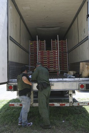 In this Aug. 13, 2017 photo, Border Patrol officers check the inside of a tractor-trailer in Edinburg, Texas. Police in Texas acting on a tip found the immigrants locked inside the tractor-trailer parked at a gas station about 20 miles (30 kilometers) from the border with Mexico, less than a month after 10 people died in the back of a hot truck with little ventilation in San Antonio. (Delcia Lopez/The Monitor via AP)