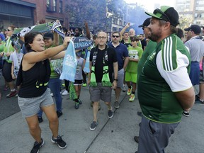 A Seattle Sounders supporter displays a scarf to supporters wearing Portland Timbers jerseys during the traditional March to the Match before an MLS soccer match between the teams Sunday, Aug. 27, 2017, in Seattle. (AP Photo/Ted S. Warren)