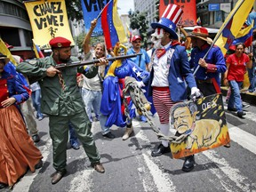 """Government supporters perform a parody involving a Venezuelan militia up against Uncle Sam, a personification of the U.S government, during an anti-imperialist march to denounce Trump's talk of a """"military option"""" for resolving the country's political crisis, in Caracas, Venezuela, Monday, Aug. 14, 2017. (AP Photo/Ariana Cubillos)"""