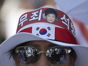 """In this Aug. 26, 2017 photo, a photo of former South Korean President Park Geun-hye is seen with letters reading """"Innocence, Release"""" on a supporter's head band during a rally to call for her release in Seoul, South Korea. A small but growing army of often elderly men and women regularly swing South Korean banners and scream outrage at the jailing of a woman they consider their spiritual mother: disgraced former President Park Geun-hye. Pro-Park demonstrations remain tiny relative to earlier protests in which millions demanded her removal from office. Her supporters refuse to accept the possibility that Park may not be the selfless daughter of South Korea she has always portrayed herself to be. (AP Photo/Lee Jin-man)"""