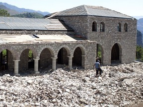 In this Tuesday, July 18, 2017, workers build a guest house in the village of Nivica, southern Albania. An ambitious project is aiming to open up remote villages in the highlands of southern Albania to the outside world and to tourists wanting to discover the spectacular natural beauty and rural way of life of the more isolated parts of the Balkan country. (AP Photo/Geo Delveroudis)