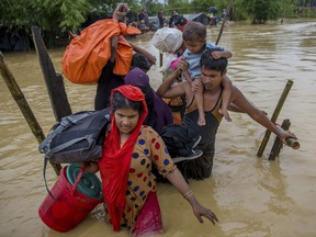 Rohingya Muslims, who crossed over from Myanmar into Bangladesh, use a makeshift footbridge as they move with their belongings after their camp was inundated with rainwater near Balukhali refugee camp, Bangladesh, Tuesday, Sept. 19, 2017. With a mass exodus of Rohingya Muslims sparking accusations of ethnic cleansing from the United Nations and others, Myanmar leader Aung San Suu Kyi on Tuesday said her country does not fear international scrutiny and invited diplomats to see some areas for themselves. (AP Photo/Dar Yasin)