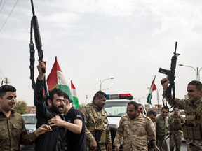 Kurdish soldiers fire their guns in the air to celebrate the independence referendum, outside a voting station on Sept. 25, 2017 in Kirkuk, Iraq.