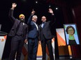 Jagmeet Singh, from left to right, Charlie Angus and Guy Caron pose for a photograph as Niki Ashton, is seen on a television screen via satellite from Ottawa, before the final federal NDP leadership debate in Vancouver on September 10, 2017.