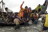 Rohingya refugees jump from a wooden boat as it begins to tip over after travelling from Myanmar, on Sept. 12, 2017 in Dakhinpara, Bangladesh.
