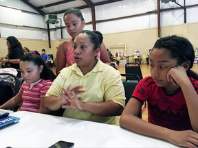 In this Sept. 2, 2017, photo, Marta Rivera, a 36-year-old Mexican woman, is surrounded by her children as she discusses Harvey's aftermath and eligibility requirements for federal disaster aid with an immigration advocate at Emmanuel Baptist Church in Houston. Many in the country illegally fear that seeking federal disaster aid will result in getting deported, prompting them to turn to places of worship and charities instead. They are ineligible for federal aid but may apply on behalf of children with legal status. The application warns parents that information may be shared with Immigration and Customs Enforcement, whose officers find and deport people. (AP Photo/Elliot Spagat)