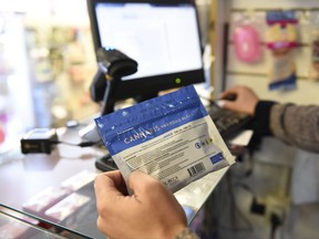 FILE - In this  July 19, 2017 file photo, a pharmacist register a bag of legal marijuana as he sells it to a customer, at a pharmacy in Montevideo, Uruguay. The country is changing its marijuana selling system because banks were making it difficult for pharmacies to sell pot as had been planned. A government official said Wednesday Sept. 13 2017, that Uruguay will set up shops to sell pot for cash and avoid the problems faced by pharmacies. (AP Photo/Matilde Campodonico, File)