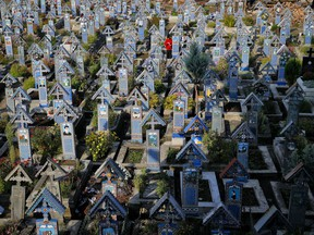 A man stands between the painted crosses in the Merry Cemetery, in Sapanta, northwestern Romania, Sunday, Sept. 10, 2017. The Merry Cemetery is a collection of more than 1,000 vivid Orthodox crosses etched with colorful epitaphs and childlike drawings and, despite its remote location, some 600 kilometers (360 miles) northwest of the Romanian capital, Bucharest, it's one of the country's top tourist attractions. (AP Photo/Vadim Ghirda)