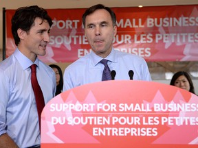 Finance Minister Bill Morneau speaks to members of the media as Prime Minister Justin Trudeau looks on at a press conference on tax reforms in Stouffville, Ont., on Monday, October 16, 2017.