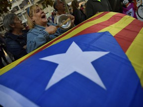 """Pro-independence supporters shout slogans in front of the Popular Party headquarters as a """"esteleda"""" or  pro-independence flag is held up, in support of the Catalonia's secession, in Pamplona, northern Spain, Friday, Oct. 6, 2017. (AP Photo/Alvaro Barrientos)"""