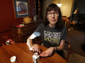 Gail Orcutt counts her medication at the kitchen table in her home, Tuesday, Oct. 17, 2017, in Pleasant Hill, Iowa. President Donald Trump's recent announcement that he's ending health subsidies for moderate-income Americans injected further uncertainty into the future of the law championed by his predecessor, Barack Obama. But confusion over open enrollment is even more pronounced in Iowa, which is seeking federal permission for a first-in-the-nation revamp of the way it administers federally mandated health care coverage and who pays for it. (AP Photo/Charlie Neibergall)