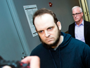 Joshua Boyle is escorted through the airport in Toronto after speaking to reporters on Friday, Oct. 13, 2017.
