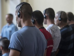FILE - In this June 21, 2017 file photo defendants stand in the courtroom at the beginning of the trial against eleven defendants charged with involvement in the death of 71 migrants who suffocated in a refrigerated truck which passed through Hungary and was discovered in Austria, near Parndorf, in 2015 at the tribunal in Kecskemet, 85 kms southeast of Budapest, Hungary. Prosecutors say an Afghan man and two Bulgarian men were part of the same trafficking organization involved in the 2015 case. (Sandor Ujvari/MTI via AP, file)