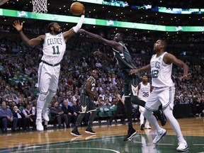 Boston Celtics guard Kyrie Irving (11) grabs a rebound against Milwaukee Bucks forward Thon Maker, center, during the first quarter of an NBA basketball game, Wednesday, Oct. 18, 2017, in Boston. At right is Boston Celtics center Al Horford. (AP Photo/Charles Krupa)