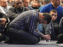 People pray in February at funeral services for three of the victims of the deadly shooting at the Quebec Islamic Cultural Centre in Quebec City.