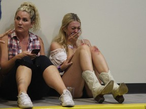 A woman cries while hiding inside the Sands Corporation plane hangar after a mass shooting in which dozens were killed at the Route 91 Harvest Festival on Sunday, Oct. 1, 2017, in Las Vegas