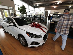 FILE - In this Friday, Oct. 6, 2017, file photo, a buyer walks past a 2018 Sonata sitting amid an assortment of models on the showroom floor of a Hyundai dealership in the south Denver suburb of Littleton, Colo. On Monday, Oct. 30, 2017, the Commerce Department issues its September report on consumer spending, which accounts for roughly 70 percent of U.S. economic activity. (AP Photo/David Zalubowski, File)