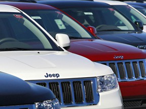 FILE - In this Nov. 30, 2010, file photo, a row of 2011 Jeep Grand Cherokee's sit at a dealership in Mesa, Ariz. Fiat Chrysler is recalling nearly 710,000 Jeep and Dodge SUVs in North America because an improperly installed brake shield could let water leak in and limit braking ability. The recall covers 2011 to 2014 Jeep Grand Cherokees and Dodge Durangos. (AP Photo/Matt York, File)