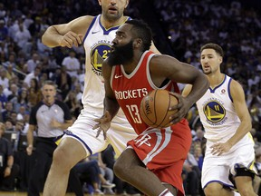 Houston Rockets' James Harden (13) drives the ball against Golden State Warriors' Zaza Pachulia, left, during the first quarter of an NBA basketball game Tuesday, Oct. 17, 2017, in Oakland, Calif. (AP Photo/Ben Margot)