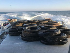 This Oct. 12, 2017, photo provided by the California Coastal Commission/UC Davis shows a pile of scrap tires after they were pulled out of the water off Balboa Peninsula in Newport Beach, Calif. Divers are removing hundreds of old tires, plastic jugs and other junk that were dumped off the Southern California coast nearly 30 years ago in hopes of creating an artificial reef that would serve as a home to fish and mussels. (California Coastal Commission/UC Davis via AP)