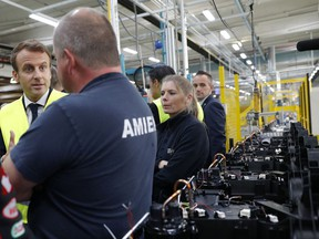 French President Emmanuel Macron talks with Whirlpool employees during a visit at the company's factory in Amiens, France, Tuesday, Oct. 3, 2017. Macron visits an ailing Whirlpool dryer factory in northern France that was the site of a pivotal moment in his presidential campaign, when he debated with angry workers about his strategy to stop job losses. (Philippe Wojazer/Pool Photo via AP)