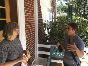 In this Saturday, Sept. 16, 2017, photo, Ashley Klingensmith, right, Pennsylvania field director for Americans for Prosperity, talks with Leora Kirkpatrick about overhauling the tax code, in Wormleysburg, Pa. Even a master salesman like President Donald Trump needs help to convince ordinary people that U.S. corporations desperately need to have their taxes cut. Which is why Klingensmith has been going door-to-door with other canvassers to ask homeowners to support lower taxes for corporations. (AP Photo/Josh Boak)