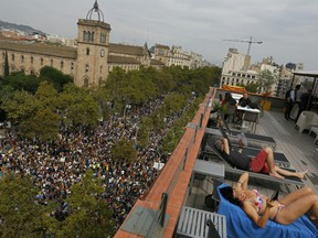 Tourists from Switzerland sunbathe at a terrace overlooking Universitat square as demonstrators gather in protest in downtown Barcelona, Spain, Tuesday Oct. 3, 2017