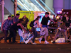 Emergency workers and festival-goers get help for an injured person after the Las Vegas shooting.