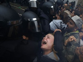 FILE -  This is a Sunday,  Oct. 1,  2017 file photo of a  girl as he  grimaces as Spanish National Police pushes away Pro-referendum supporters outside the Ramon Llull school assigned to be a polling station by the Catalan government in Barcelona, Spain. For local teacher Elisa Aroca, Sunday will go down as the day when Spain lost the battle for the hearts and minds of Catalonia. (AP Photo/Emilio Morenatti/File)
