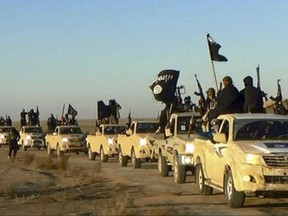 Militants of the Islamic State group hold up their weapons and wave its flags on their vehicles in a convoy to Iraq, in Raqqa, Syria in an undated photo