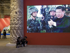 In this Thursday, Oct. 19, 2017, photo, video showing Chinese President Xi Jinping handling an assault rifle is shown at an exhibition highlighting China's achievements under five years of his leadership at the Beijing Exhibition Hall in Beijing. Xi is channeling a red-blooded nationalism as he seeks to strengthen the Communist Party's role in Chinese life and assert Beijing's rise as a global superpower. Xi's muscular foreign policy could become even more assertive following this month's party congress, where he's expected to get a second five-year term as party secretary general. (AP Photo/Ng Han Guan)