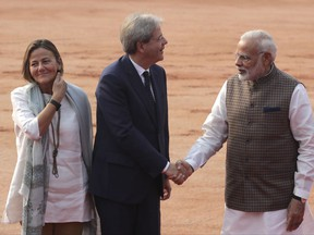 Indian Prime Minister Narendra Modi, right, shakes hand with his Italian counterpart Paolo Gentiloni, center, as Gentiloni's wife Emanuela Mauro watches during their ceremonial reception at the Indian presidential palace in New Delhi, India, Monday, Oct. 30, 2017. Gentiloni is on a two day state visit to India. (AP Photo/Manish Swarup)