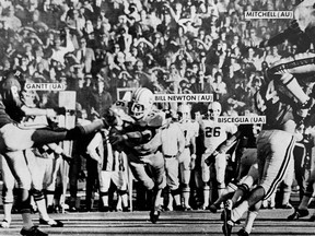 FILE - In this Dec. 2, 1972, file photo, Auburn's Bill Newton, center, blocks an Alabama  puns in the fourth quarter of the Iron Bowl NCAA college football game at Legion field in Birmingham, Ala., that resulted in an Auburn touchdown. (Haywood Paravicini/AL.com via AP, File)