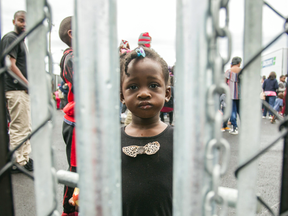 A girl who crossed the U.S. border into Canada illegally with her family, claiming refugee status, looks through a fence at a temporary detention centre in Blackpool, Quebec, in August.