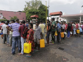 Sri Lankans stand in a queue to buy gasoline near a fuel station during a fuel shortage in Colombo, Sri Lanka, Tuesday, Nov. 7, 2017. Sri Lankans Tuesday stood in long lines for the fourth straight day to buy gasoline amid a fuel shortage. (AP Photo/Eranga Jayawardena)