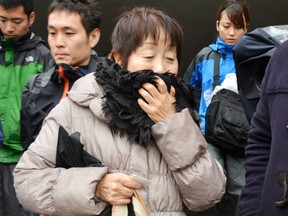 In this undated photo, Chisako Kakehi, centre, answers to a reporter's question in Sakai, western Japan. A Japanese court has sentenced the woman to hang in a serial poisoning murder case targeting elderly men, including her husband.