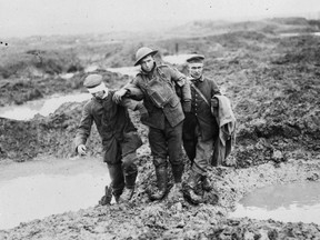 A Canadian and two German prisoners of war struggle through the mud of Passchendaele.