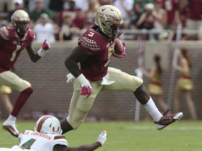 FILE - In this Oct. 7, 2017, file photo,Florida State's Jacques Patrick eludes Miami's Jaquan Johnson to gain yardage in the first quarter of an NCAA college football game,in Tallahassee, Fla.  Florida State's offense has been decimated by injuries, but the Seminoles are getting a rare bit of good news. Running back Jacques Patrick was feared lost for the season after an injury on Oct. 21 against Louisville but indications are he could be back when the Seminoles travel to No. 3 Clemson on Saturday. (AP Photo/Steve Cannon, File)