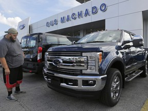 FILE - In this Tuesday, Jan. 17, 2017, file photo, a potential customer looks at a Ford F-250 Lariat FX4 at a Ford dealership, in Hialeah, Fla. Ford posted a big sales jump in October 2017 but Fiat Chrysler and General Motors reported declines as auto companies started to report numbers Wednesday, Nov. 1. The drop by two of the Detroit Three backs analysts' expectations that September's big gain in U.S. auto sales would fizzle in October. (AP Photo/Alan Diaz, File)