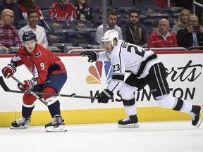 Los Angeles Kings right wing Dustin Brown (23) and Washington Capitals defenseman Dmitry Orlov (9), of Russia, watch the puck during the first period of an NHL hockey game, Thursday, Nov. 30, 2017, in Washington. (AP Photo/Nick Wass)