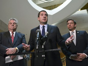 FILE - In this Oct. 24, 2017, file photo, House Intelligence Committee Chairman Rep. Devin Nunes, R-Calif., center, standing with Rep. Peter King, R-N.Y., left, and Rep. Ron DeSantis, R-Fla., right, speaks on Capitol Hill in Washington. As Congress returns from its Thanksgiving break, some Republicans would like to wrap up investigations into Russian meddling in the 2016 election that have dragged on for most of the year. But with new details in the probe emerging on an almost daily basis, that timeline seems unlikely. (AP Photo/Susan Walsh, File)