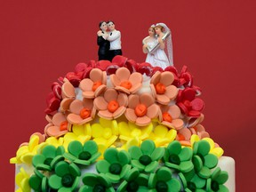 A wedding cake in rainbow colours and decorated with two same-sex couples.